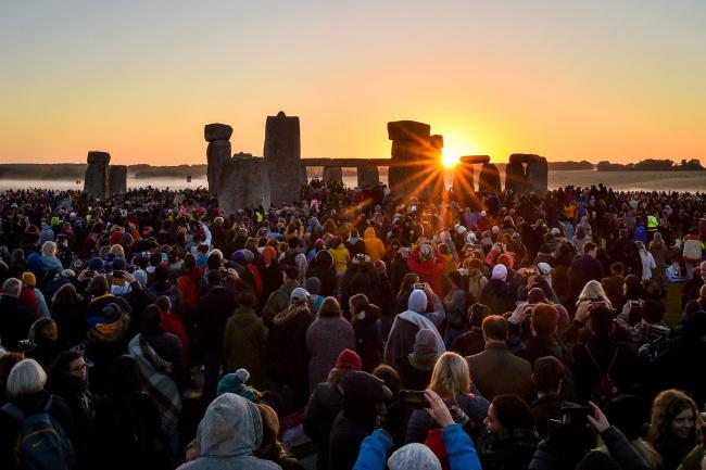 The sun rises between the stones and over crowds at Stonehenge