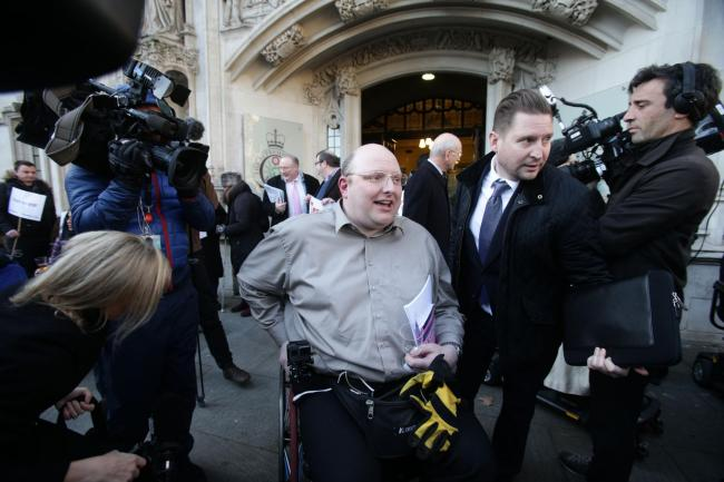 Doug Paulley (centre), from Wetherby, West Yorkshire, outside the Supreme Court in London, after disabled travellers won a partial victory at the court in their battle for priority use of wheelchair spaces on buses. PRESS ASSOCIATION Photo. Picture date: