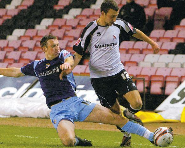 SLIDING CHALLENGE: Darlington's Josh Gray is dispossessed by Port Vale's Lee Collins on Tuesday night