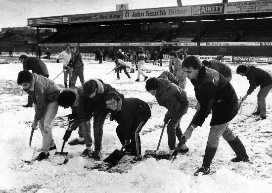 York City fans clear the snow from the pitch at Bootham Crescent in 1985