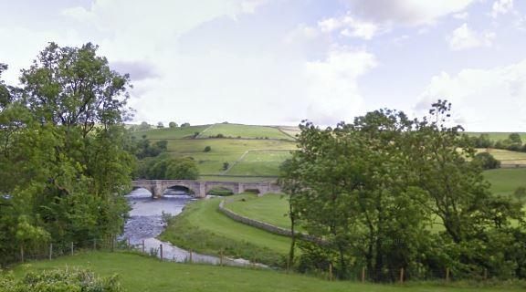 The grass car park beside Burnsall Bridge