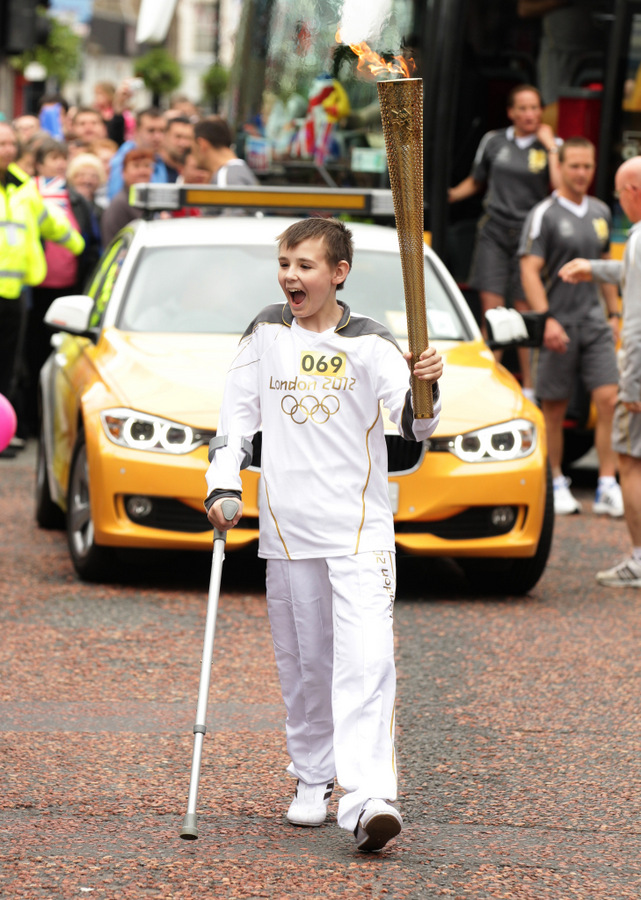 Kieran pictured proudly carrying the Olympic flame through Bishop Auckland