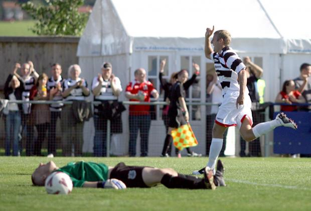Flat Out: Bishop Auckland keeper Peter Jeffries lies on the deck as Darlington's David Dowson reels away in celebration after adding the last of  Quakers ' three goals