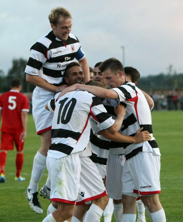 Off the mark: Darlington players mob Chris Emms after putting Darlington ahead last night