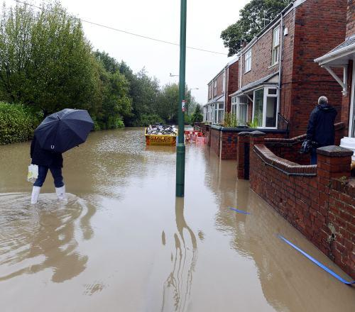 Darlington and Stockton Times: Residents make their way through flood water in Chester-le-Street.