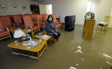 Lauren Cochrane, 12, sits in a flooded room as heavy rainfall causes damage to properties in Gilling West, North Yorkshire.