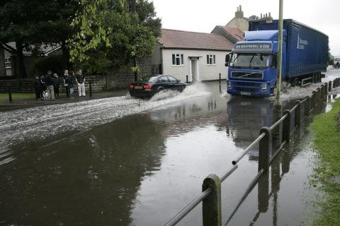 MAKING WAVES: Vehicles brave the floodwater in Croft yesterday