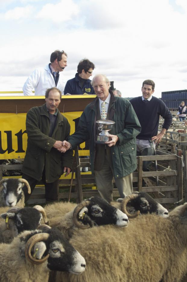 CONGRATULATIONS: Peter Woodall, right, presents the Rosebowl to upland sheep farmer Stuart Wood