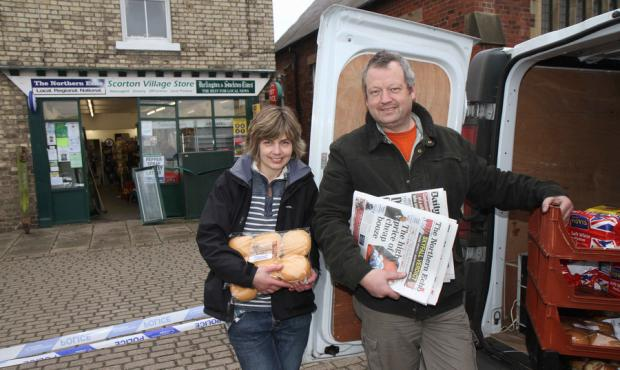 STILL SMILING: Fiona and Tony Simms sell bread and newspapers from their van after the raid