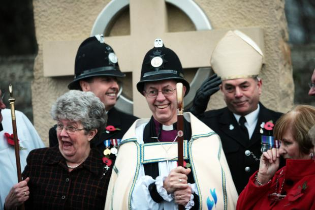 Darlington and Stockton Times: HATS OFF: Justin Welby swaps hats with local beat officer PC Keith Todd after blessing the new market cross in Sedgefield. The bishop invited PC Todd and his colleague, Sergeant Brian O'Connor, to pose for a photograph with him