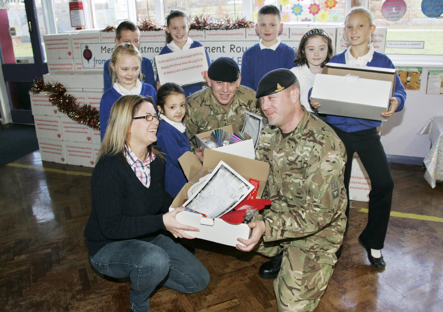 GIFTS FOR THE TROOPS: Organiser Nikki Gaynor and some of the pupils hand over the bo