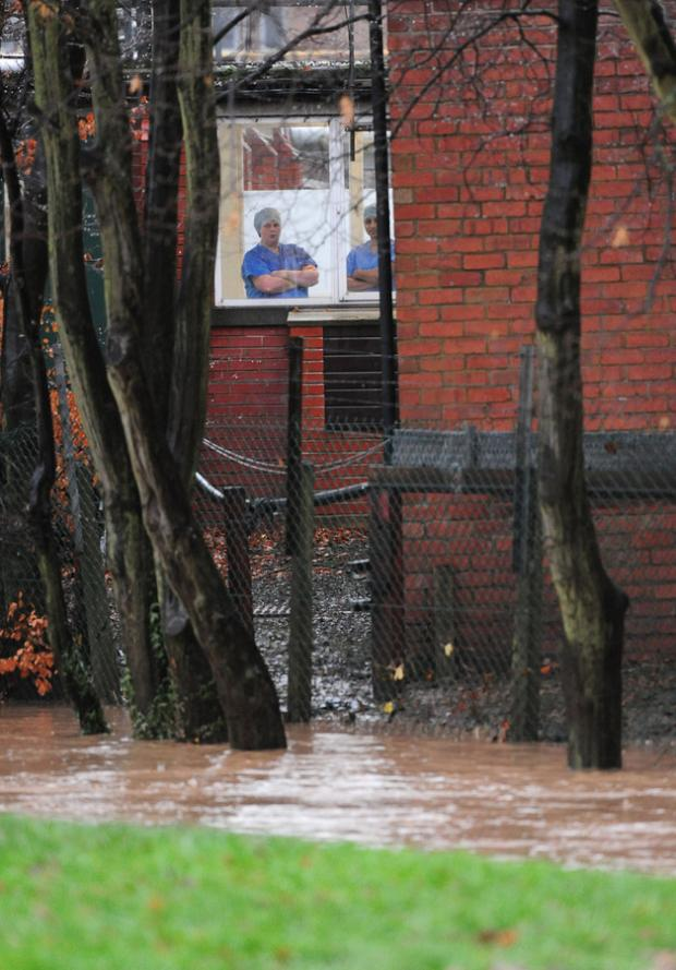 Darlington and Stockton Times: GRIM CONDITIONS: Medical staff look out of a window over the beck at the Friarage hospital, in Northallerton, as the heavy rain continues
