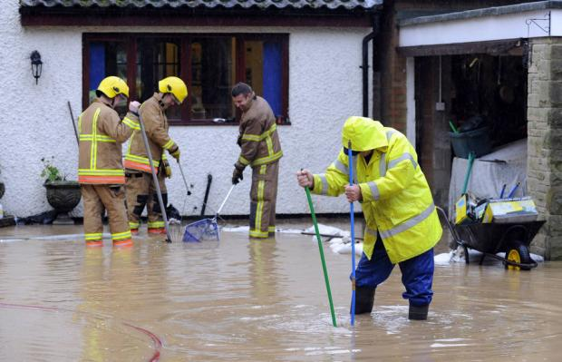 Darlington and Stockton Times: RISING WATER: Fire and rescue workers, helped by local volunteers, try to clear flooding from around Mike Walker's house, in Middleton St George, near Darlington
