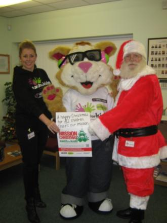 Deniece Wanley, Charity Manager at Cash for Kids, with mascot Courage the Cat and Santa at the launch of Mission Christmas
