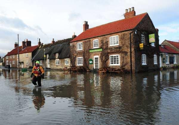 Darlington and Stockton Times: Fire fighters in the flooded streets of Old Malton, North Yorkshire, yesterday