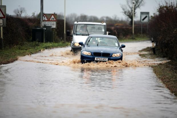 COMING THROUGH: Motorists make their way along the flooded Roundhill Road in Hurworth near Darlington after floods made travelling difficult