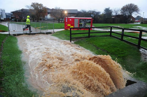 Darlington and Stockton Times: PUMPING OUT: Firefighters prepare to pump water away from a beck behind the Friarage Hospital in Northallerton