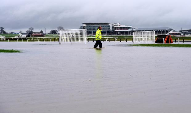 Darlington and Stockton Times: WET GOING: Head groundsman Ian Ward wades through floodwater on the track following torrential rain at Wetherby Racecourse