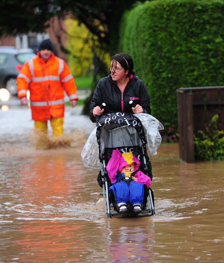 SWAMPED: A woman pushes a child in a pushchair through floodwater in Northallerton