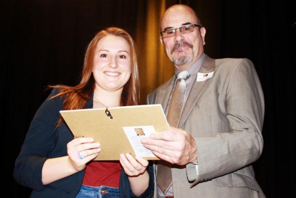 Katie Roe receiving the Bob Carnell Award for most significant contribution to school life, presented by Griff Hosker, a local author.