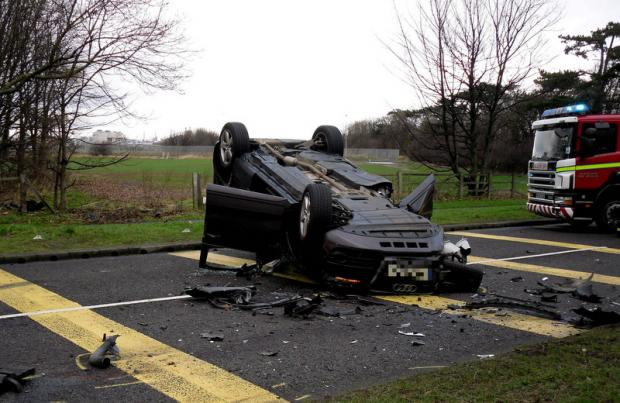 ROAD HORROR: A car on its roof at the scene of yesterday's crash on the A174. Police said at least four cars were involved in the accident
