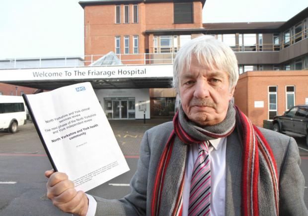 ANGER: Coun John Blackie with the NHS report which cost £320,000.
