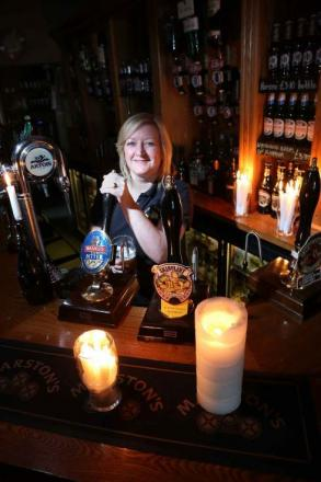 Landlady Ann Marsh pours beer by candlelight in the blackout at the Coach and Horses