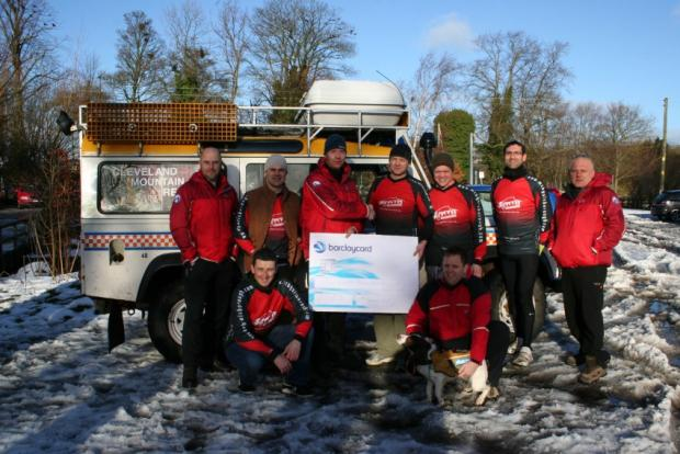 Guisborough mountain biker Rory Spence presents a cheque to Cleveland Mountain Rescue team leader, Mal Selby with other members of the Rescue including search dog Fern.