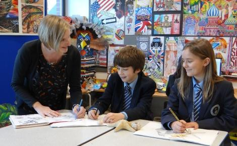 Caption: Melanie Kane, curriculum leader for art with year seven pupils, Loukas Vassilounis (left) and Jagoda Wieckiewicz