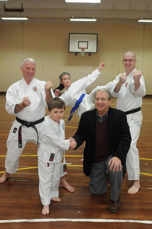 Sho Shin Kai Karate Club member Ethan Loverance shakes hands with Allan McCall, a Co-operative Durham area committee member. They are pictured with (L to R) Ron Gibson, chief instructor, Nicole Knappett, club member, and Gordon Rooney, club secretary.