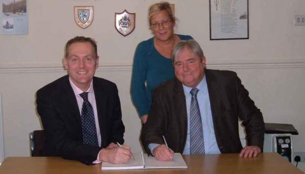 DEAL SIGNED: Andy Preston of Green Lane Capital, Town Council chairman Councillor Ian Dalgarno and Councillor Tina Large sign the deal