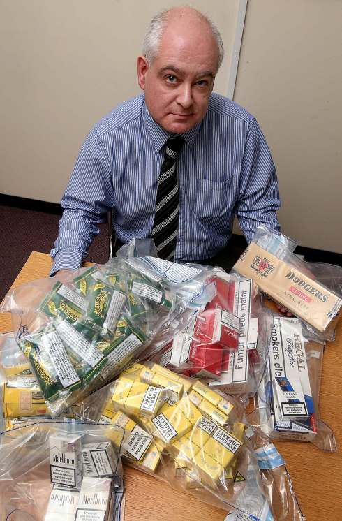 Fair Trading officer Shaun Trevor with some of the counterfeit cigarettes seized during the raid.