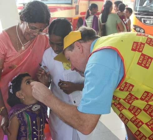 CAPTION: Rotarian Tony Jordan administers the polio vaccine to a child in Kerala, India.