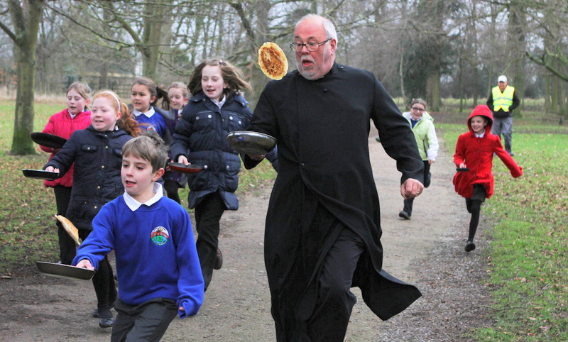 FLIP AND RUN: The Reverend Ian Robinson competes – and loses – in the Bedale Pancake Race.