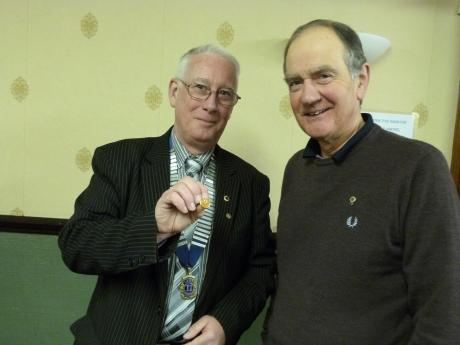 Tony Gent, Darlington Lions President presents Richard Western with a crystal pin in recognition of his achievements