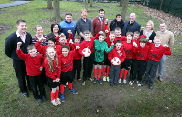 Darlington FC manager Martin Gray (blue tracksuit) with pupils from Mount Pleasant School after receiving their new football kits from Darlington Community Advice Partnership