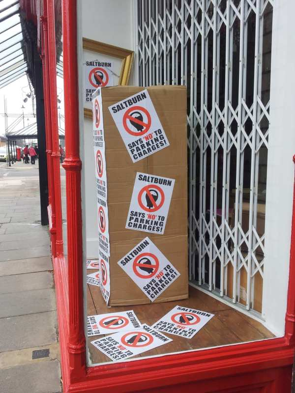 A shop window in Saltburn covered in anti-parking charge posters