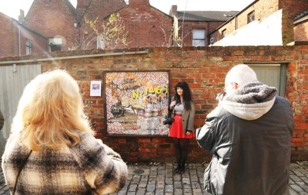 BACKSTREET SHOW: Art student Rebecca Robinson has her photo taken in front of her work