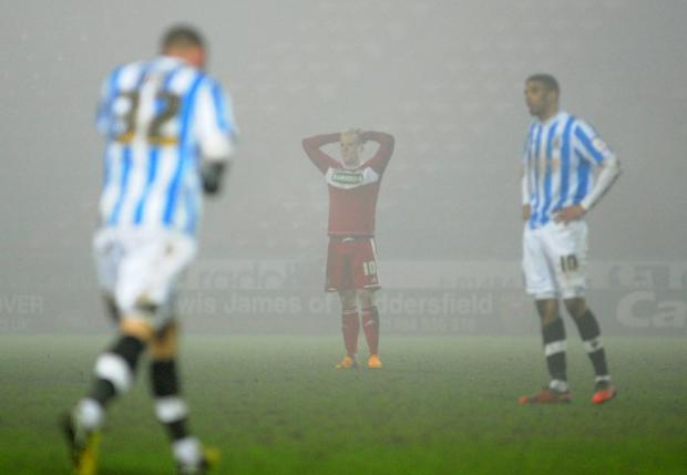 MIST OPPORTUNITY: Middlesbrough's Nicky Bailey appears dejected after Huddersfield grab two late goals snatch the points on the night when freezing fog swirled around the stadium