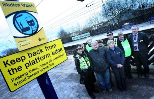 Members of the Samaritans and British Transport Police stand next to a new Samaritans poster on the platform at Northallerton train station