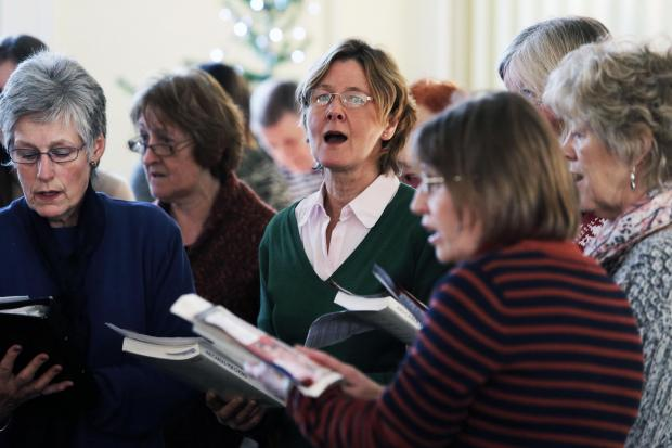 Members of the St. Peter's Church Choir sing during a Christmas market at The Croft Hotel