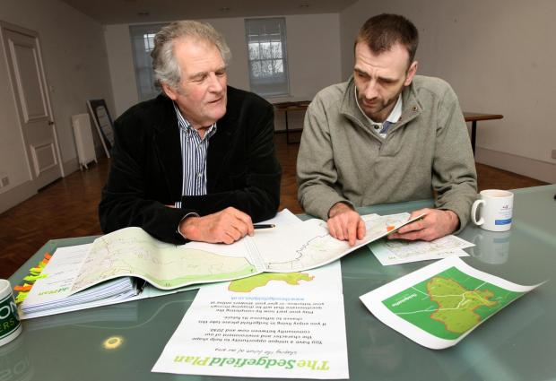 Business man David Bowles (l) and Chris Lines (r) look over the plans for the Sedgefield Plan.