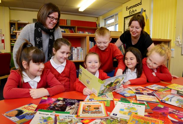 Darlington and Stockton Times: BOOK WORMS: Rebecca Sedgwick and Sarah Meeson from Teesdale Housing Association help Evenwood pupils with their reading