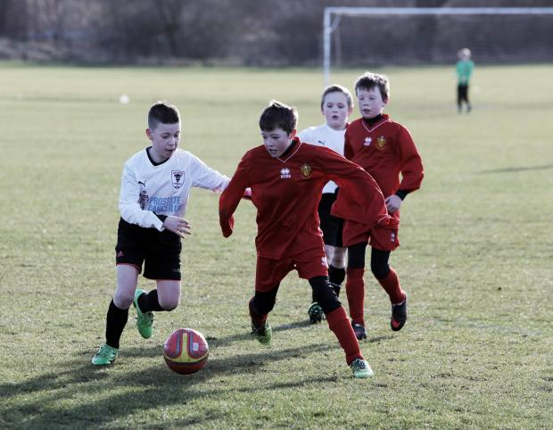 ON THE BALL: Darlington Young Bulls FC under 11s, in white, against Richmond Town