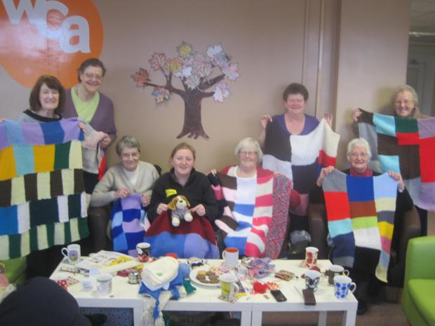 Knitters from Willington Community Action's Knit and Knatter group display their dog blankets