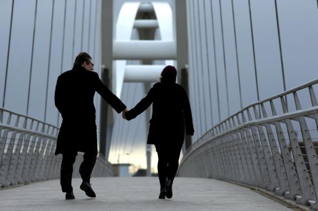 Chris Webber and his date step out on the Infinity Bridge in Stockton