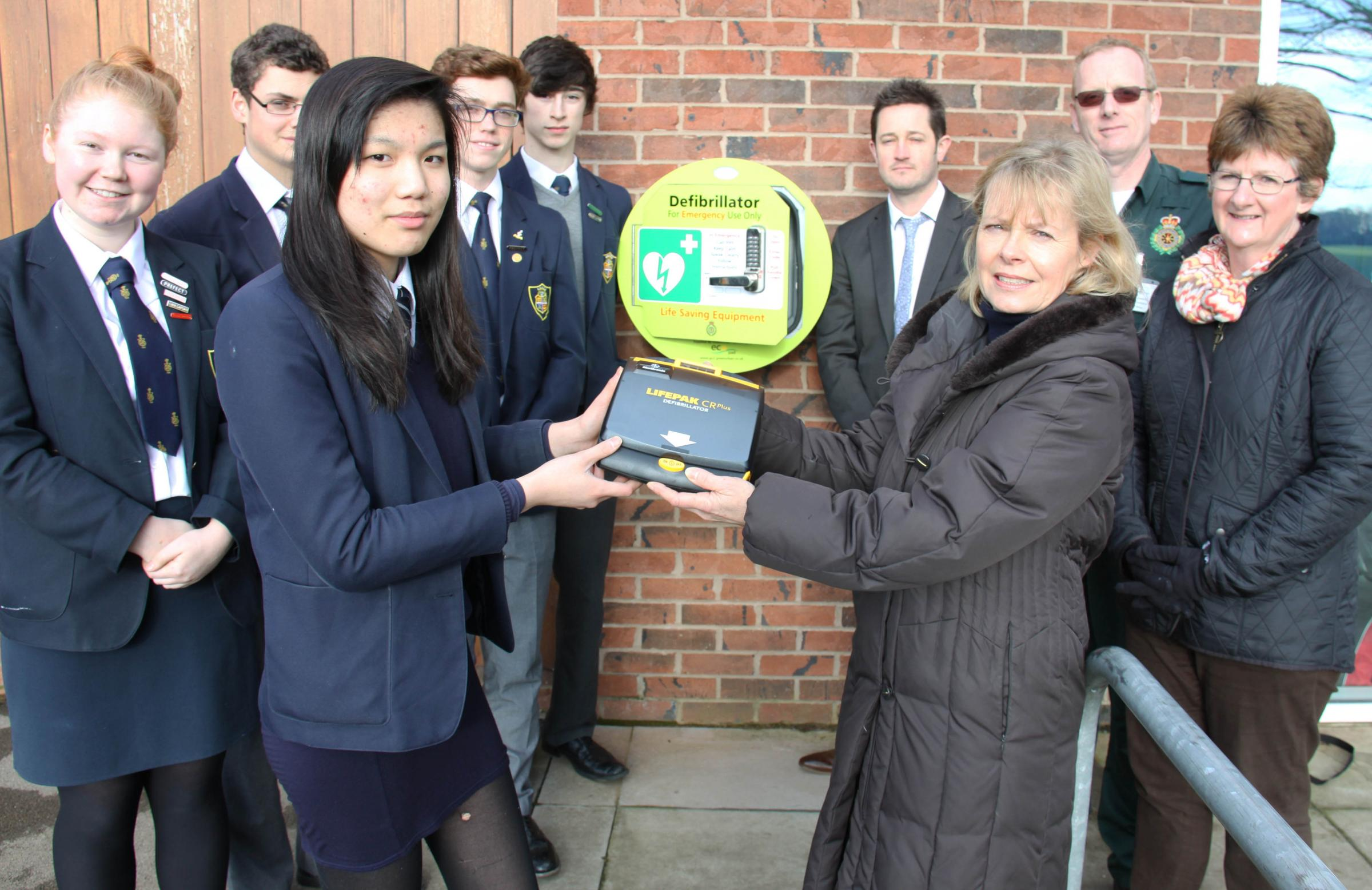 Alison Reed, of the parents' association, passes the defibrillator to student Lory Wong as sixth formers look on together with  Chris Sharp and Neil Marsey, of the ambulance Service, and Fiona Pearman, of the association