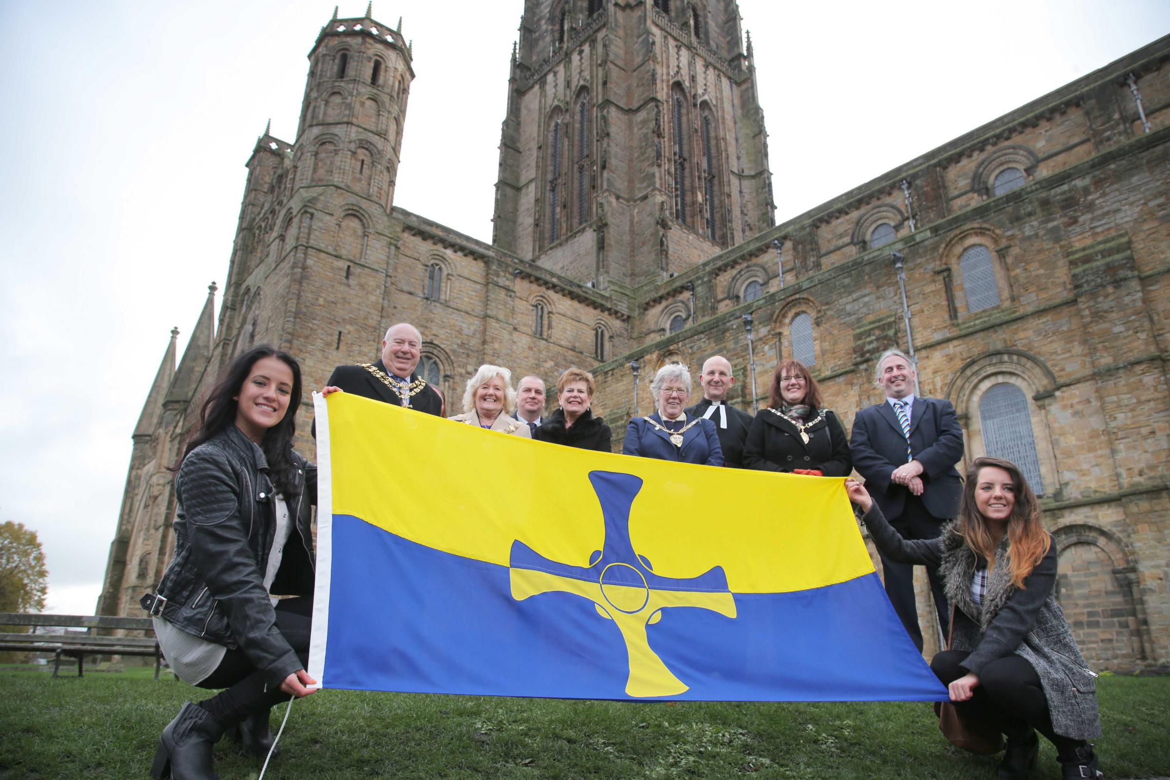 Durham flag designers Katie, left, and twin sister Holly Moffatt from Chilton hold the new flag at Durham Cathedral with dignitaries in background.