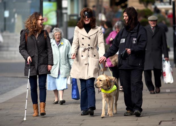 Jenny Chapman MP (centre) perfroms a blind-folded walk in connection with the RNIB.  Also pictured are Adele Waterfall-Brown (left, RNIB volunteer/campaign co-ordinator), Shelly Sherrington (right, guide dog mobility instructor) and guide dog Locky
