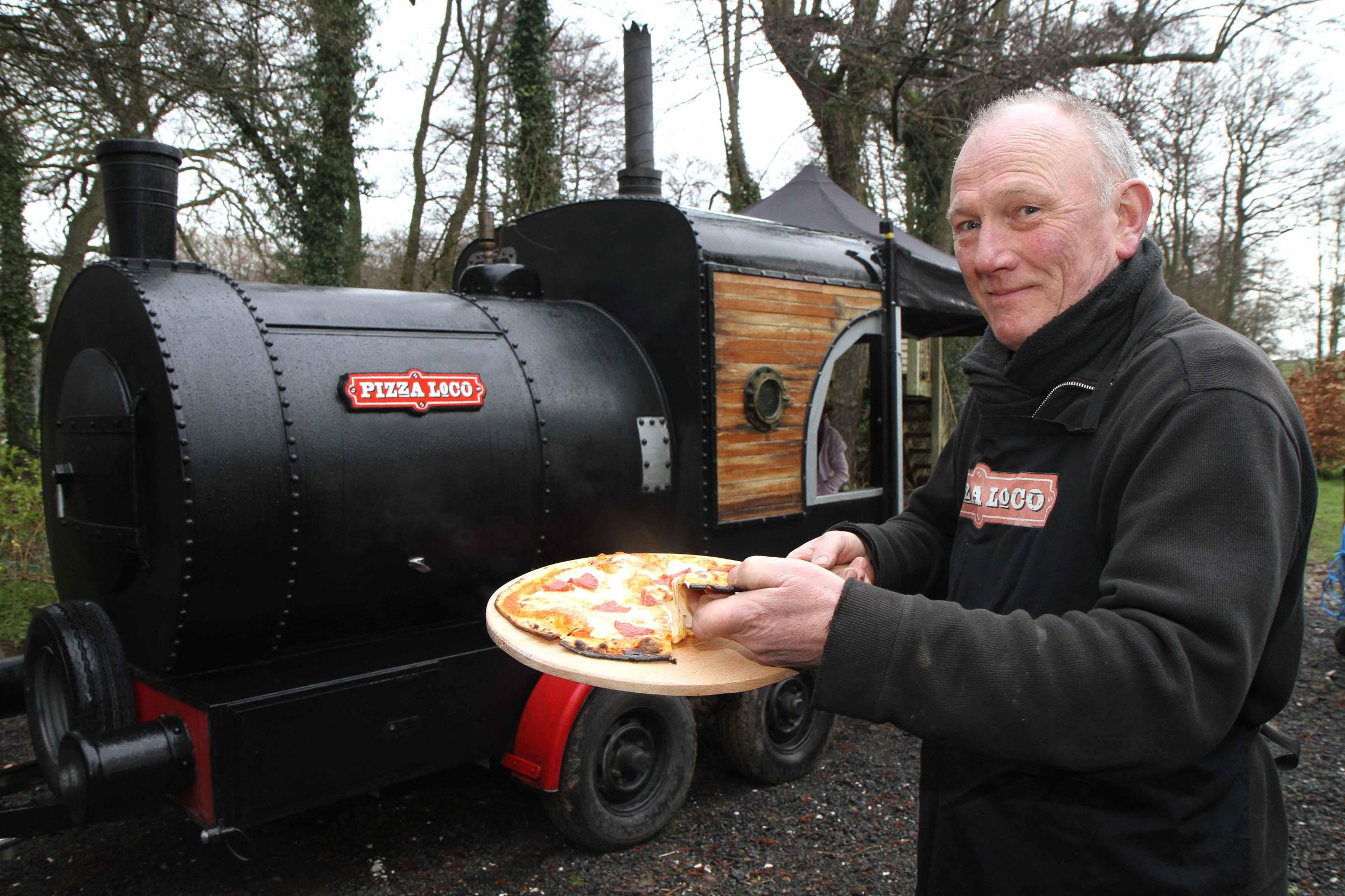 "FULL STEAM AHEAD: Owner Paul Bulmer, of Pizza Loco, with his ""steam train"", a former cattle trailer, which has a wood-burning stove for cooking pizzas"